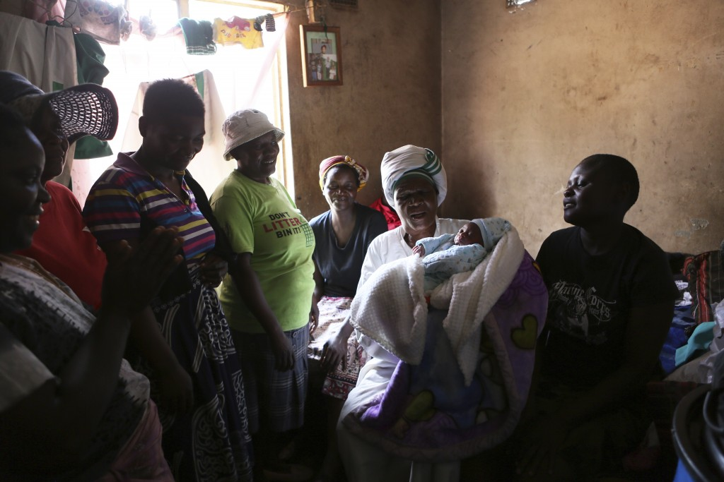 72-year old grandmother Esther Zinyoro Gwena holds one of the babies she helped deliver in her tiny apartment in the poor surburb of Mbare in Harare, ...