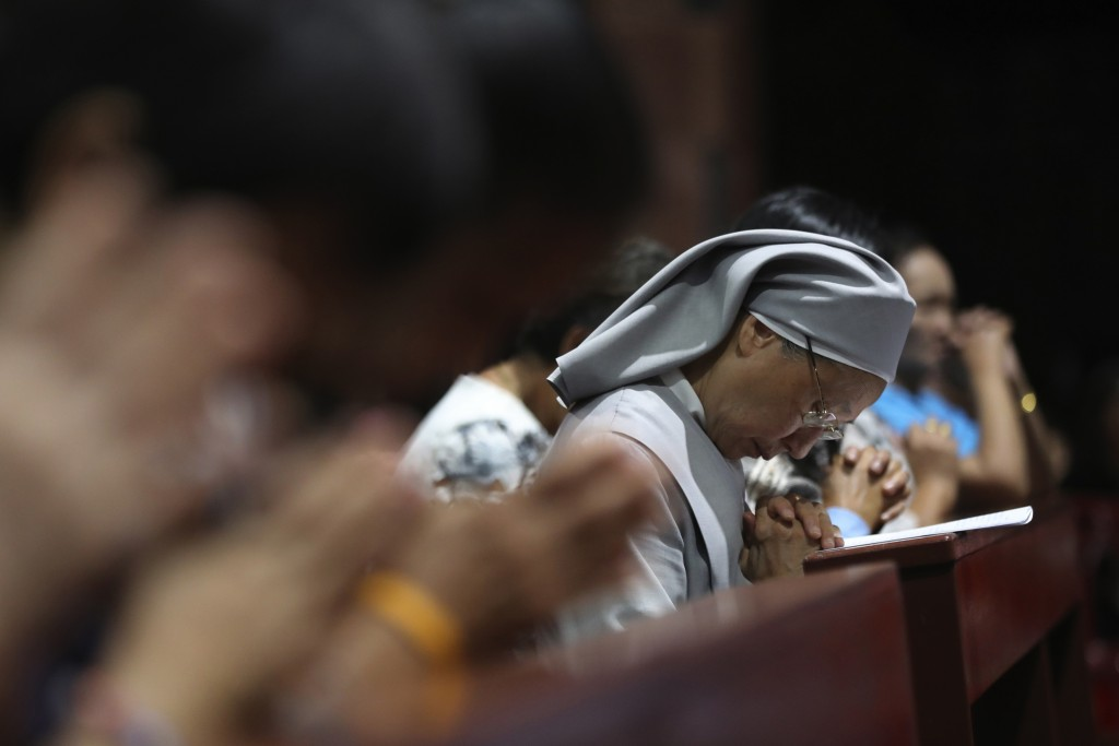 In this Friday, Oct. 18, 2019, photo, Catholic devotees and nuns pray at the Christ Church during the 30th anniversary of the beatification of seven m...