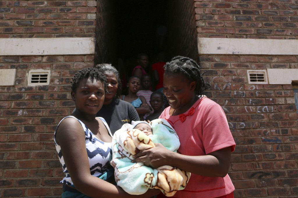 Perseverance Kanyoza, left, shows her newly delivered baby, after the birth in a tiny apartment in the poor suburb of Mbare in Harare, Zimbabwe, Satur...