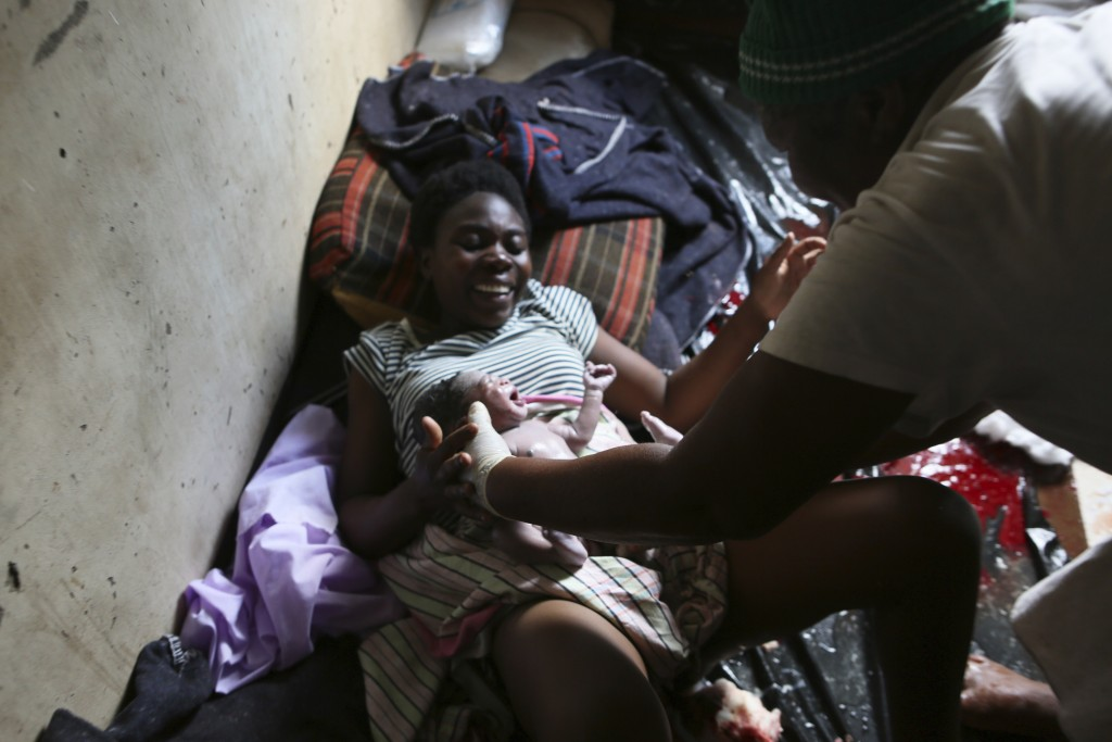 Samantha Nazarere smiles as she is handed her new baby, delivered in a tiny apartment in the poor Mbare suburb in Harare, Zimbabwe, Saturday, Nov. 16,...