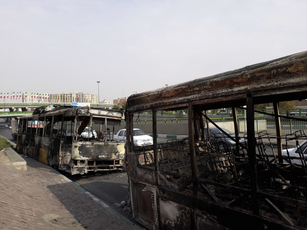 This photo released by the Iranian Students' News Agency, ISNA, shows scorched public buses that remained on the street after protests that followed a...