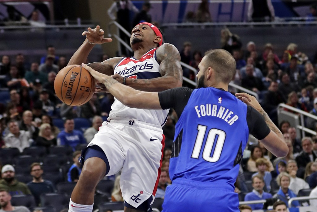 Orlando Magic's Evan Fournier (10) knocks the ball away from Washington Wizards' Bradley Beal as he goes up for a shot during the first half of an NBA...