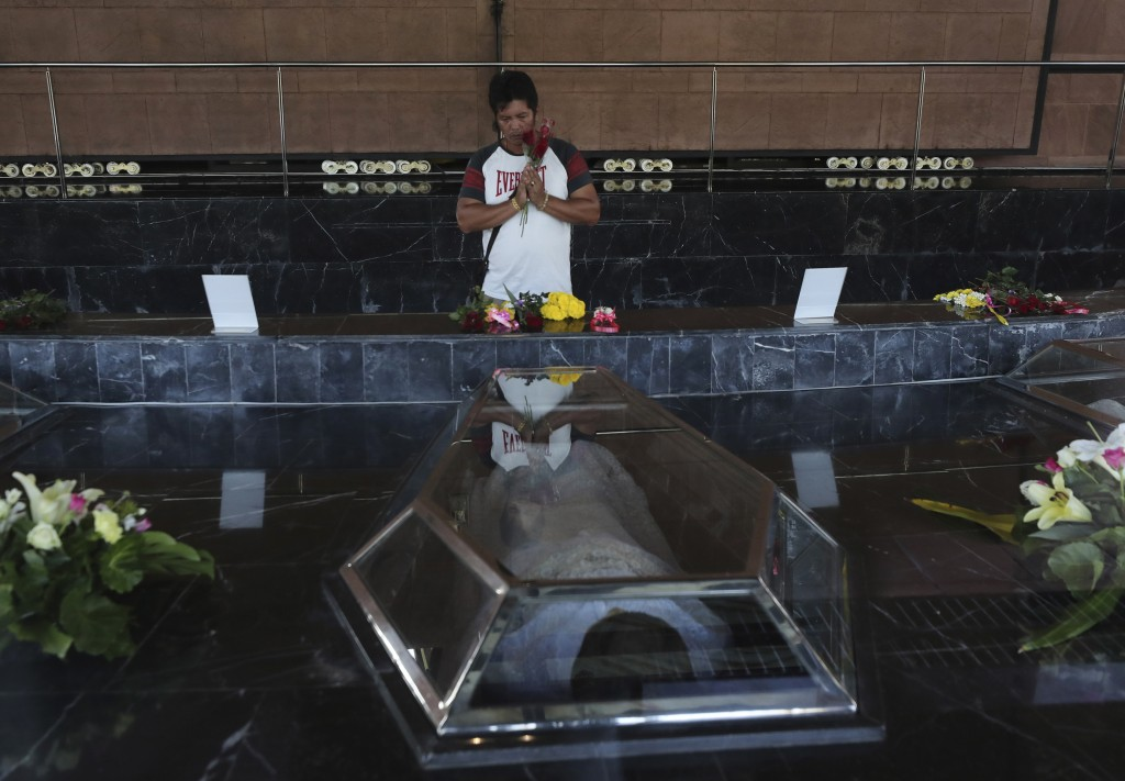 In this Friday, Oct. 18, 2019, photo, a Catholic devotee prays in front of glass caskets containing the seven replicas of the Blessed Martyrs for Chri...