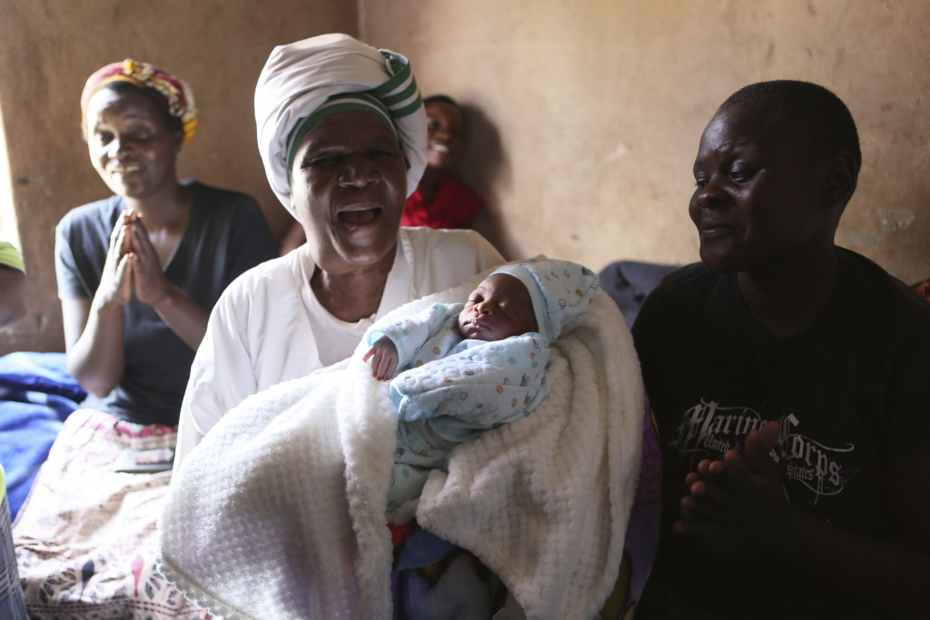 Esther Zinyoro Gwena holds one of the babies she has just delivered in her tiny apartment in the poor suburb of Mbare in Harare, Zimbabwe, Saturday, N...