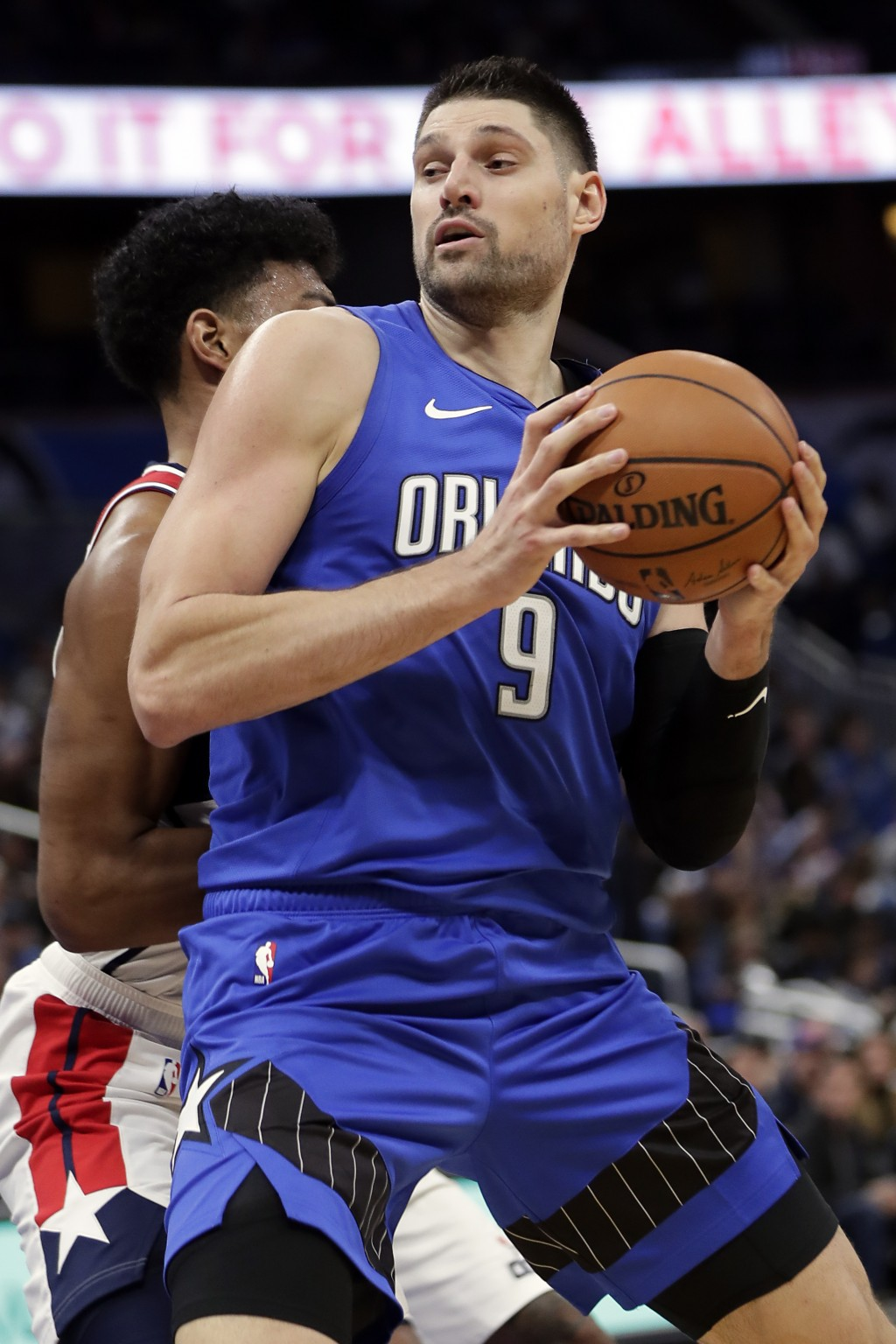 Orlando Magic's Nikola Vucevic (9) makes a move to the basket against Washington Wizards' Rui Hachimura, left, during the second half of an NBA basket...