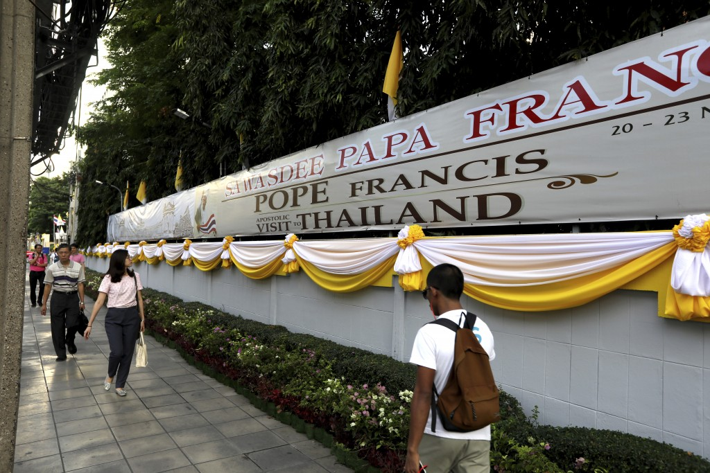 People walk past a banner welcoming Pope Francis in Bangkok, Thailand, Tuesday, Nov. 19, 2019. Pope Francis arrives in Thailand on Wednesday for the f...