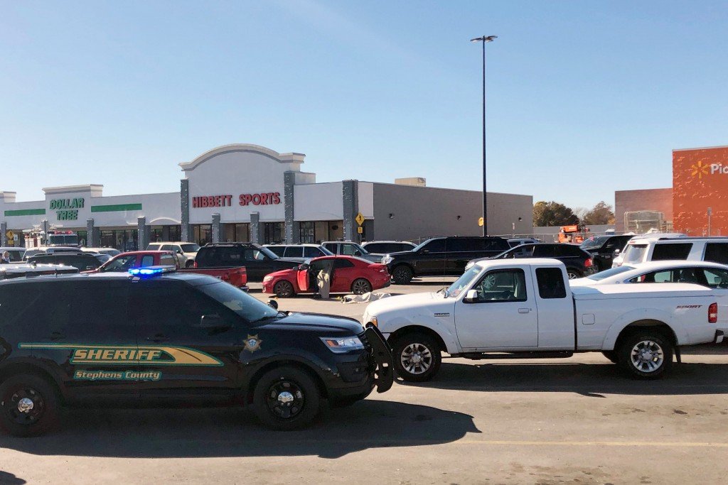 Law enforcement work the scene where two men and a woman were fatally shot Monday, Nov. 18, 2019, outside a Walmart store in Duncan, Okla. Two victims...