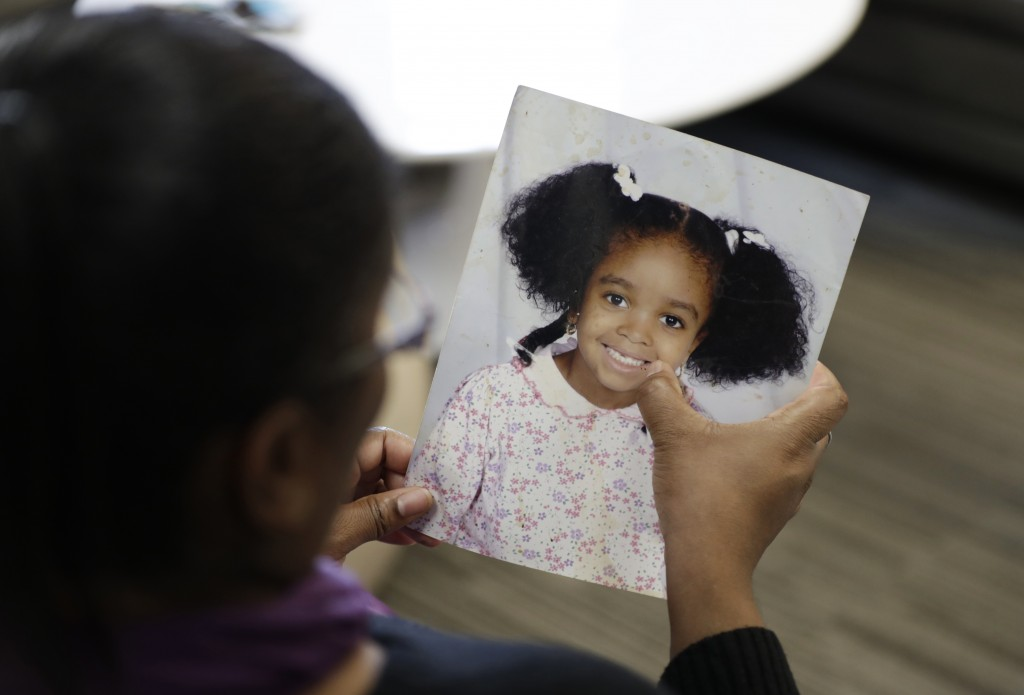 In this Oct. 29, 2019, photo, Donnesha Cooper touches a photo of her daughter, Alianna DeFreeze, in Cleveland. Her daughter's murder and the murder of...