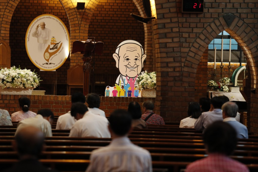 People pray at the Assumption Cathedral as a caricature of Pope Francis is placed alongside in Bangkok, Thailand, Tuesday, Nov. 19, 2019. Pope Francis...