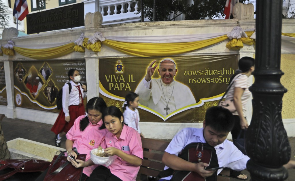 Students wait for transportation next to a poster of Pope Francis in Bangkok, Thailand, Tuesday, Nov. 19, 2019. Pope Francis arrives in Thailand on We...