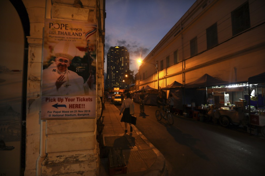 A girl walks past Pope Francis poster pasted on a wall near Assumption cathedral in Bangkok, Thailand, Tuesday, Nov. 19, 2019. Pope Francis arrives in...