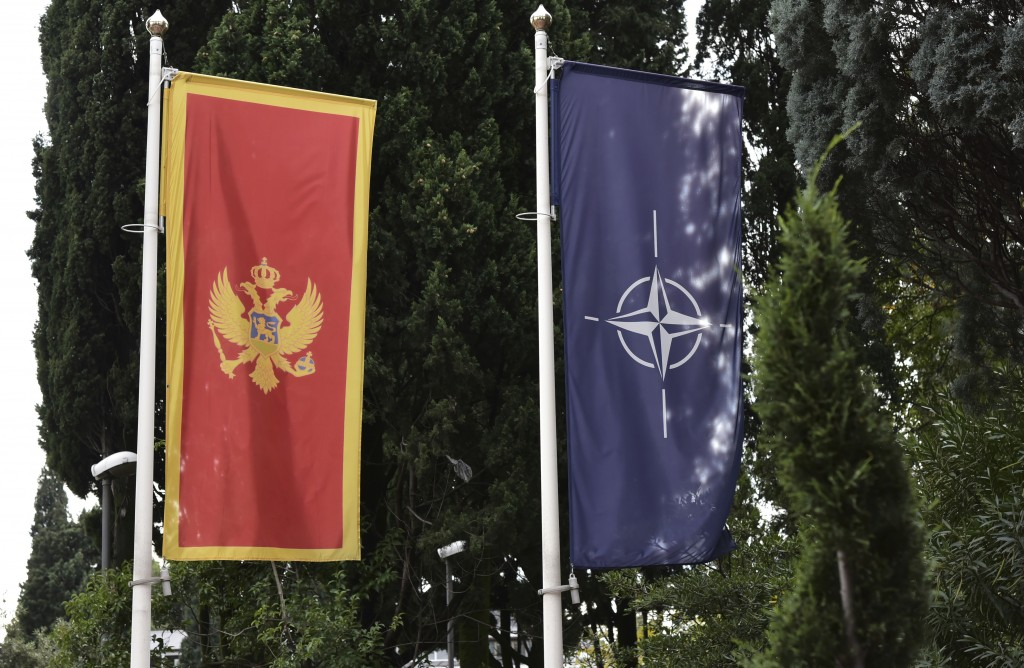 In this photo taken Monday, Nov. 11, 2019, the Montenegro, left, and NATO flags wave in front of the Montenegrin Defense Ministry in Podgorica, Monten...