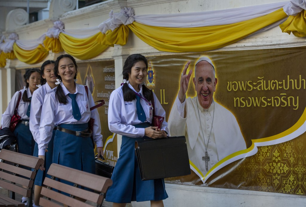 School children walk in Assumption Cathedral courtyard, decorated with posters of Pope Francis in Bangkok, Thailand, Wednesday, Nov. 20, 2019. Pope Fr...