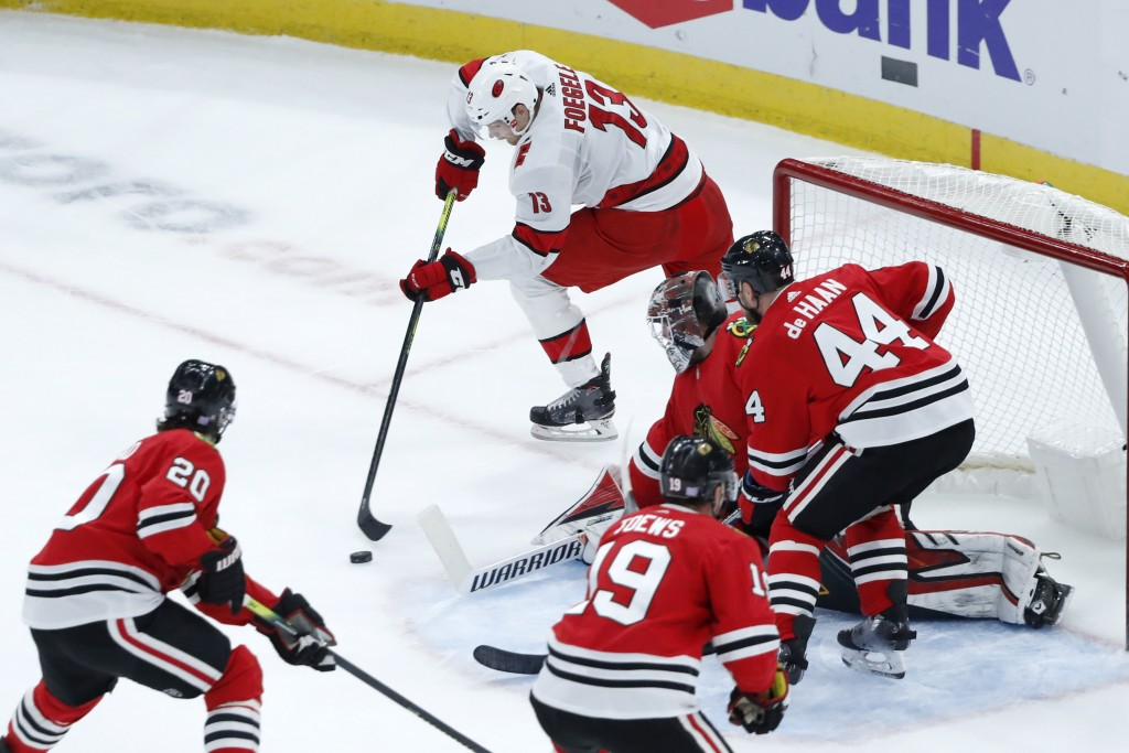 Carolina Hurricanes left wing Warren Foegele (13) takes a backhand shot on goal as Chicago Blackhawks defend during the first period of an NHL hockey ...