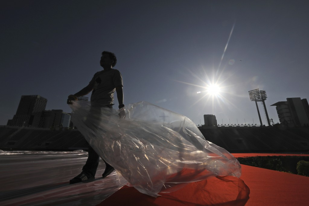 A workers covers the main stage where Pope Francis is scheduled to conduct holy mass on Thursday, with plastic to save it from dust and water in Bangk...