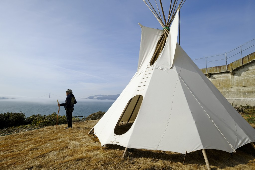 In this photo taken Tuesday, Nov. 12, 2019, Eloy Martinez, who took part in the Native American occupation of Alcatraz 50 years earlier, stands by a t...