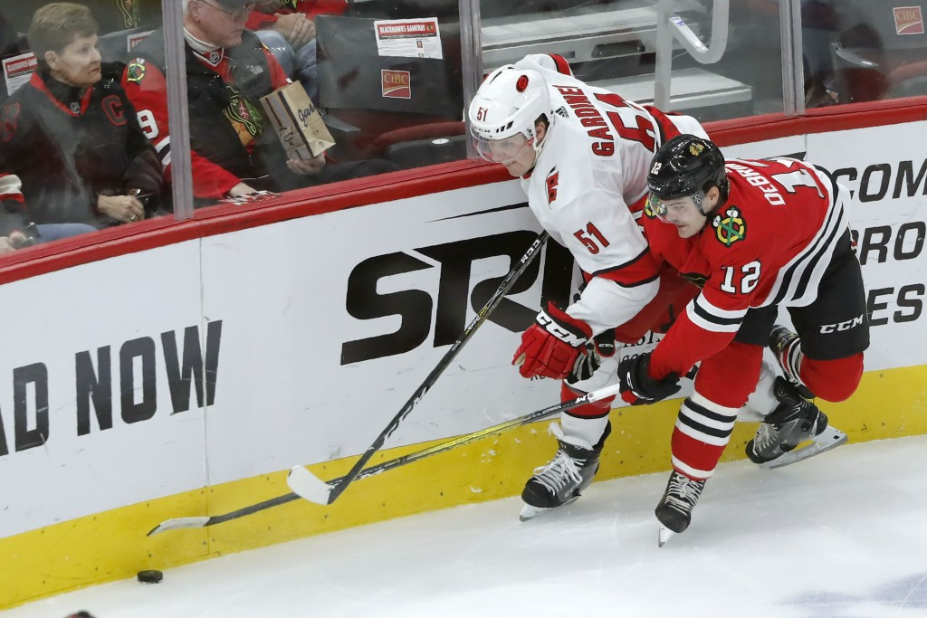 Carolina Hurricanes' Jake Gardiner (51) and Chicago Blackhawks' Alex DeBrincat vie for the puck during the first period of an NHL hockey game Tuesday,...