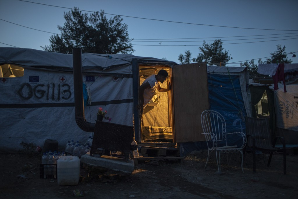 In this Thursday Oct. 3, 2019 photo, an Afghan man looks out of his tent in a makeshift refugee and migrant camp on the fringes of the overcrowded Mor...