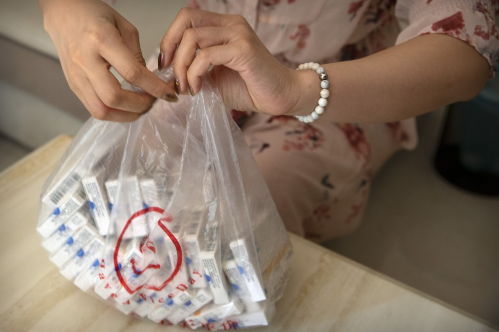 A woman holds a plastic bag of OxyContin tablets sold in China in southern China's Hunan province on Sept. 24, 2019. Representatives from the Sacklers...
