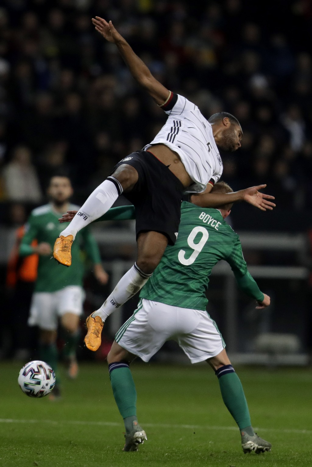 Germany's Jonathan Tah, front, jumps for the ball by Northern Ireland's Liam Boyce during the Group C soccer qualifying match between Germany and Nort...