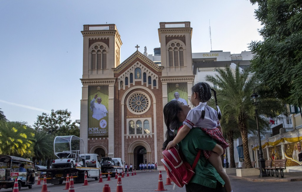 A woman carries a child across Assumption Cathedral courtyard, decorated with posters of Pope Francis in Bangkok, Thailand, Wednesday, Nov. 20, 2019. ...