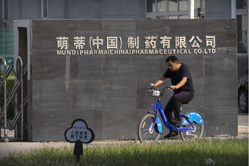 A man rides a bicycle past the entrance gate of a Mundipharma facility in an industrial park on the outskirts of Beijing, China on Sept. 27, 2019. As ...