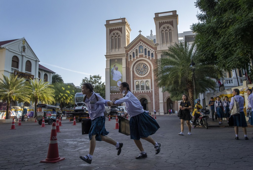 School children run in the courtyard of Assumption Cathedral, decorated with posters of Pope Francis in Bangkok, Thailand, Wednesday, Nov. 20, 2019. P...