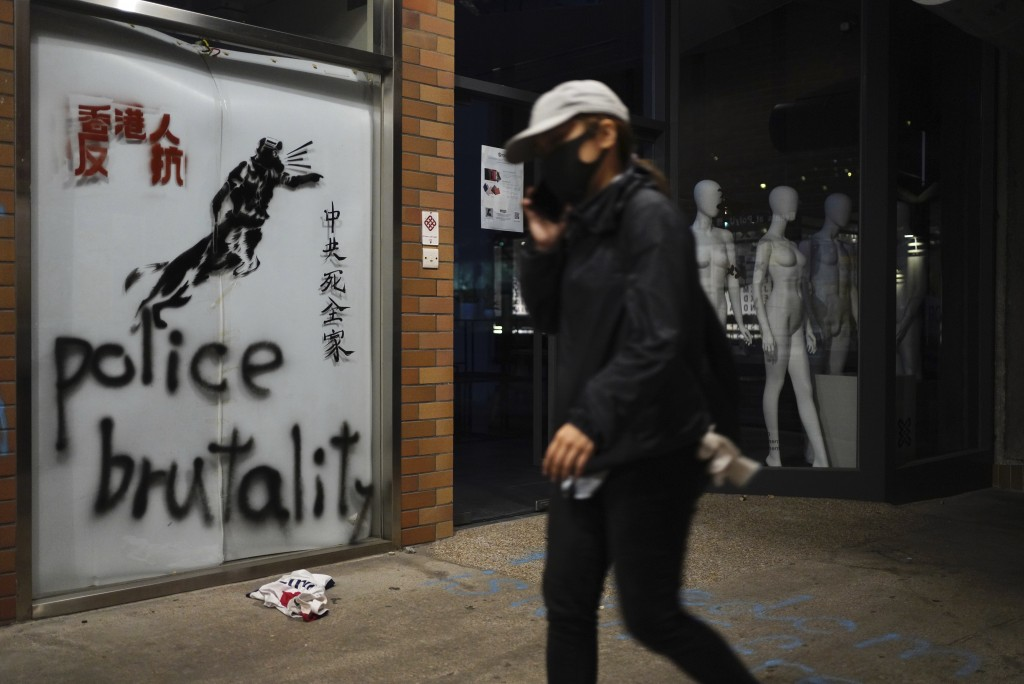 "A protester walks past graffiti depicting police as a dog and various slogans including ""Hongkongers Resist, ""Chinese Communist whole family die"" at t..."