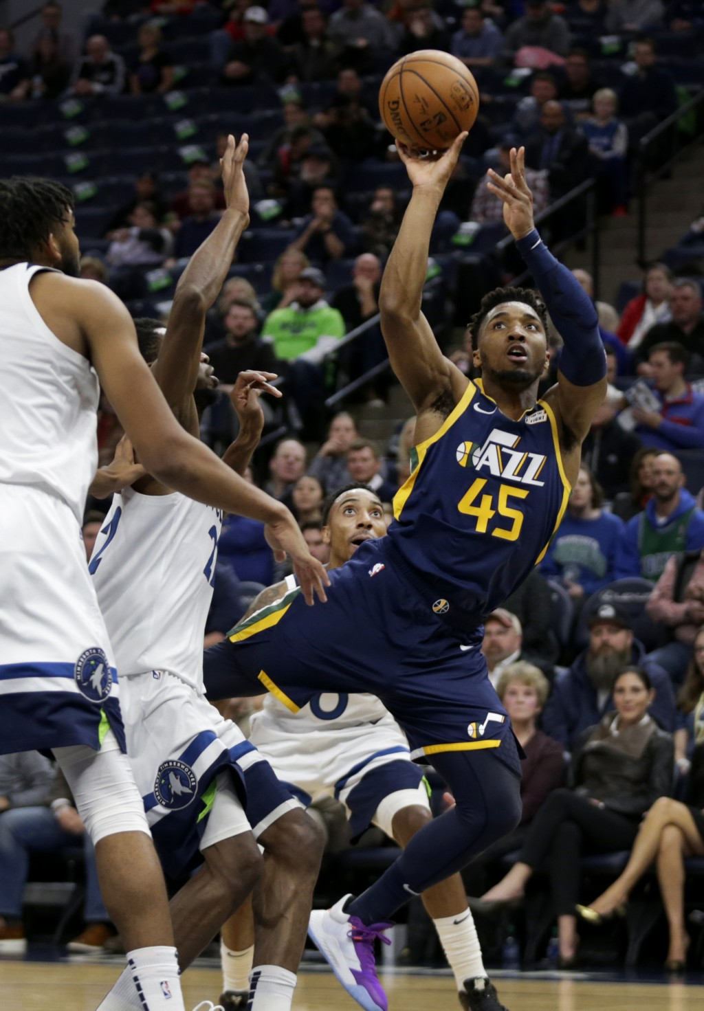 Utah Jazz guard Donovan Mitchell (45) shoots past Minnesota Timberwolves center Karl-Anthony Towns, left, forward Andrew Wiggins (22) and guard Jeff T...