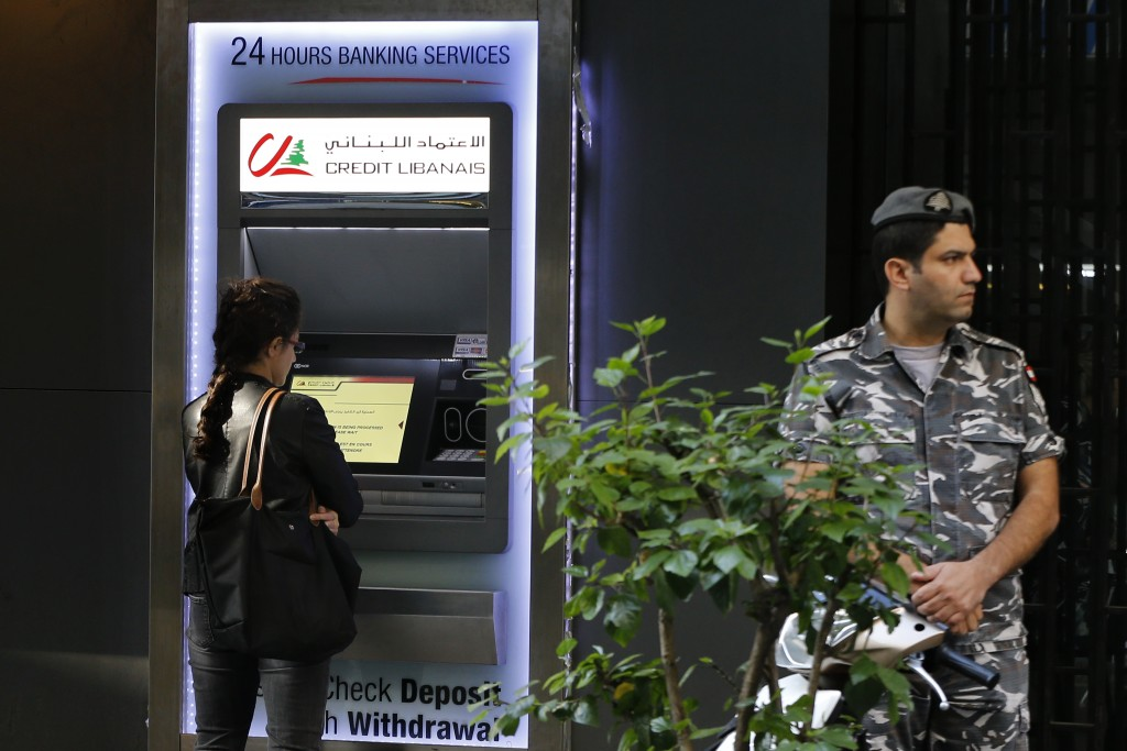 A woman uses ATM outside a bank, as a Lebanese policeman stands guard, in Beirut, Lebanon, Wednesday, Nov. 20, 2019. Lebanon's worsening financial cri...