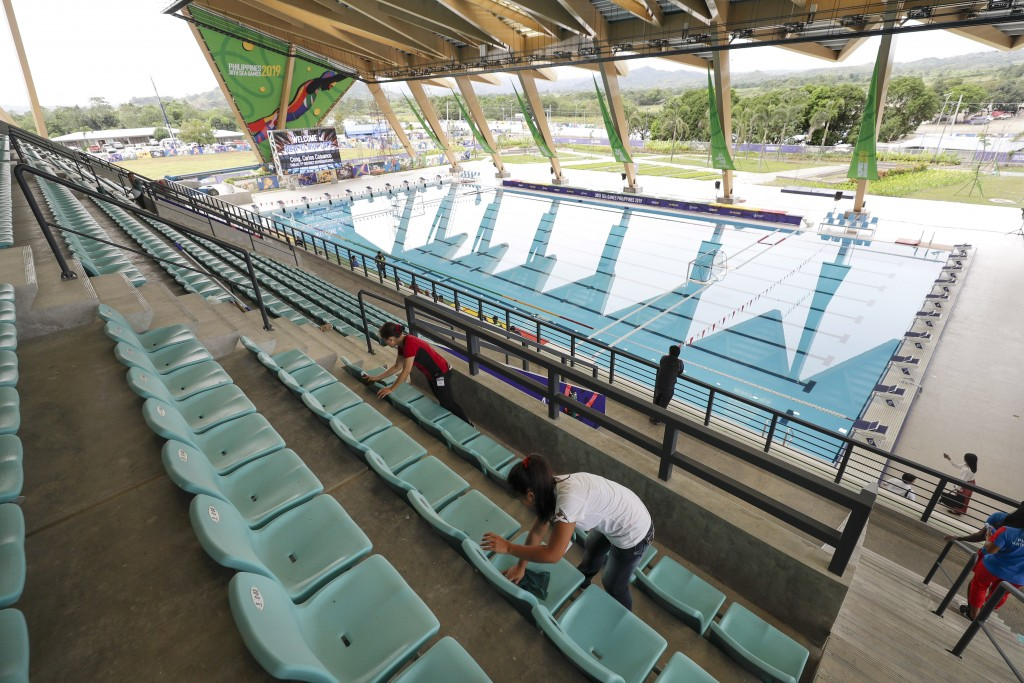 Workers clean the newly built Aquatics Center as they prepare for the 30th Southeast Asian Games at the New Clark City, Tarlac province, northern Phil...