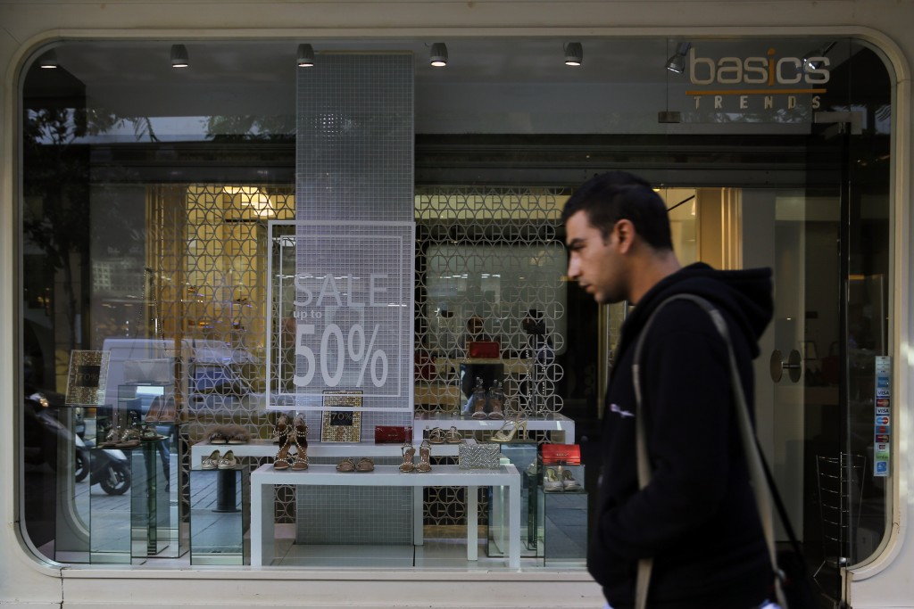 A man walks past a sign advertising a sale, in Beirut, Lebanon, Wednesday, Nov. 20, 2019. Lebanon's worsening financial crisis has thrown businesses a...