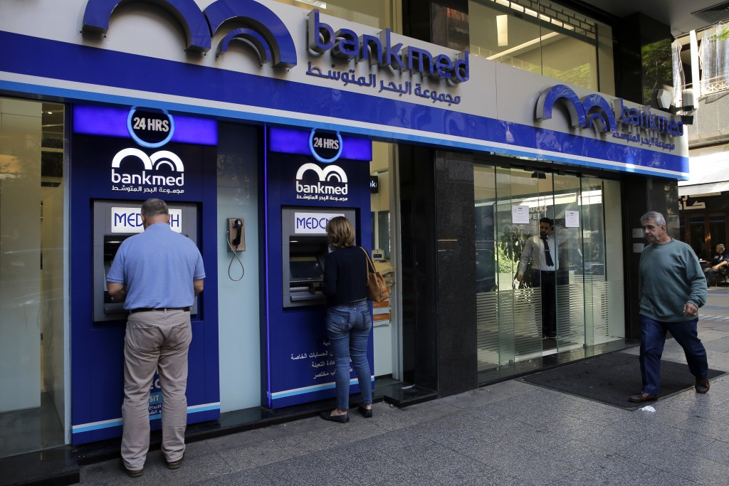 People use an ATM outside a bank, in Beirut, Lebanon, Wednesday, Nov. 20, 2019. Lebanon's worsening financial crisis has thrown businesses and househo...