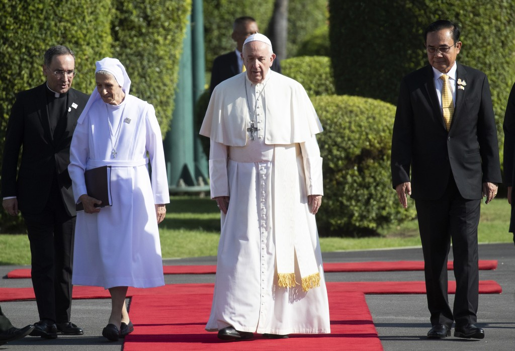 Pope Francis, center, walks with his cousin Ana Rosa Sivori, left, and Thailand's Prime Minister Prayuth Chan-ocha, right, during a welcoming ceremony...