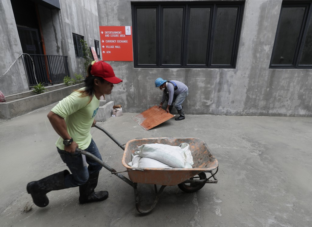 Workers rush to finish the Athlete's Village as they prepare for the 30th South East Asian Games at the New Clark City, Tarlac province, northern Phil...
