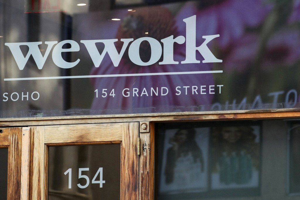 FILE - This Oct. 15, 2019, file photo shows a WeWork logo at the entrance to one of their office spaces in the SoHo neighborhood of New York. WeWork i...