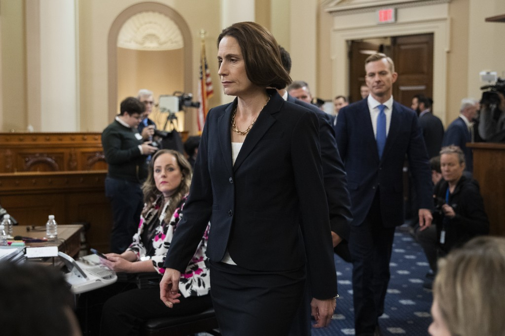 Former White House national security aide Fiona Hill, and David Holmes, a U.S. diplomat in Ukraine, back right, walk to their seats to testify before ...