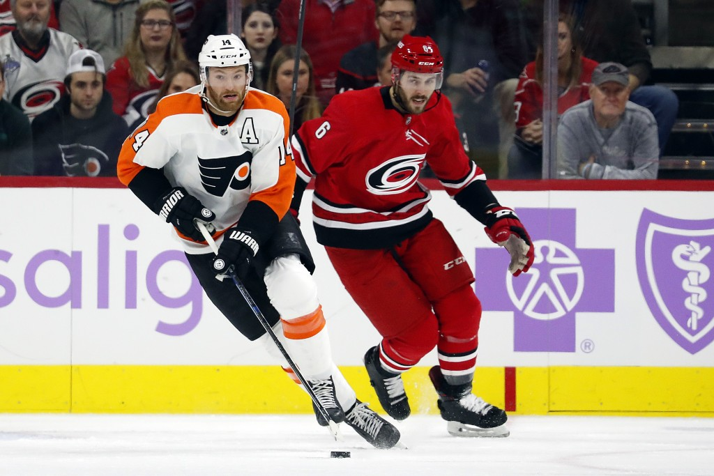 Philadelphia Flyers' Sean Couturier (14) brings the puck up the ice after taking it from Carolina Hurricanes' Joel Edmundson (6) during the first peri...