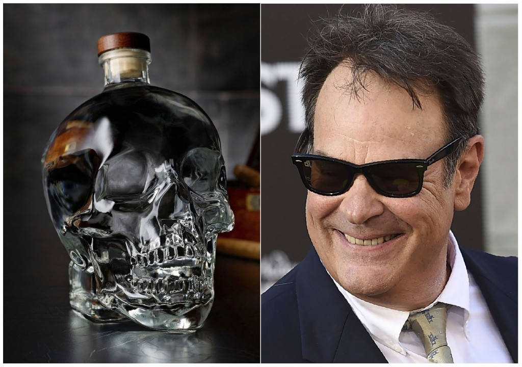 """This combination photo shows actor and businessman Dan Aykroyd at the Los Angeles premiere of """"Ghostbusters"""" on July 9, 2016, right, and a bottle of h..."""