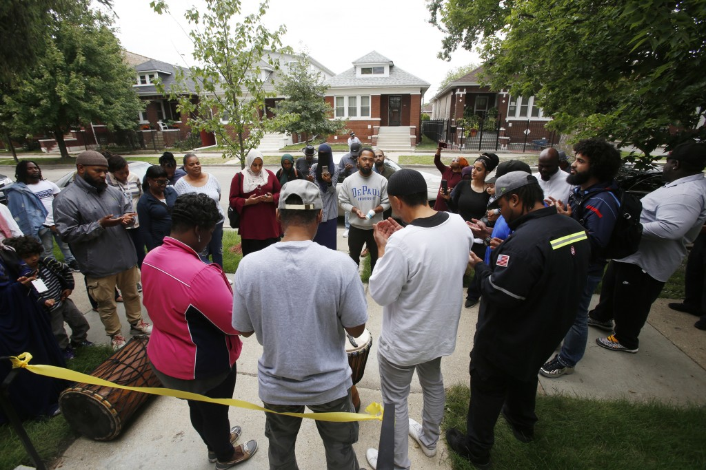Mary and Hassan Smith, center with backs to camera, pray with well-wishers outside their newly rehabbed home in the Chicago Lawn neighborhood of Chica...