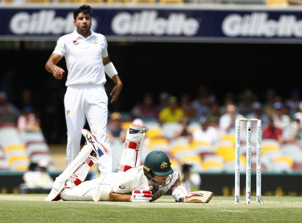 Australia's Joe Burns, front, falls after slipping in his crease as Pakistan's Imran Khan, back, watches on during their cricket test match in Brisban...
