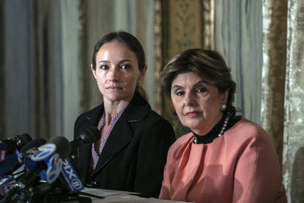 Teala Davies, left, and her attorney Gloria Allred, right, listen during a news conference, Thursday, Nov. 21, 2019, in New York, about the filing of ...