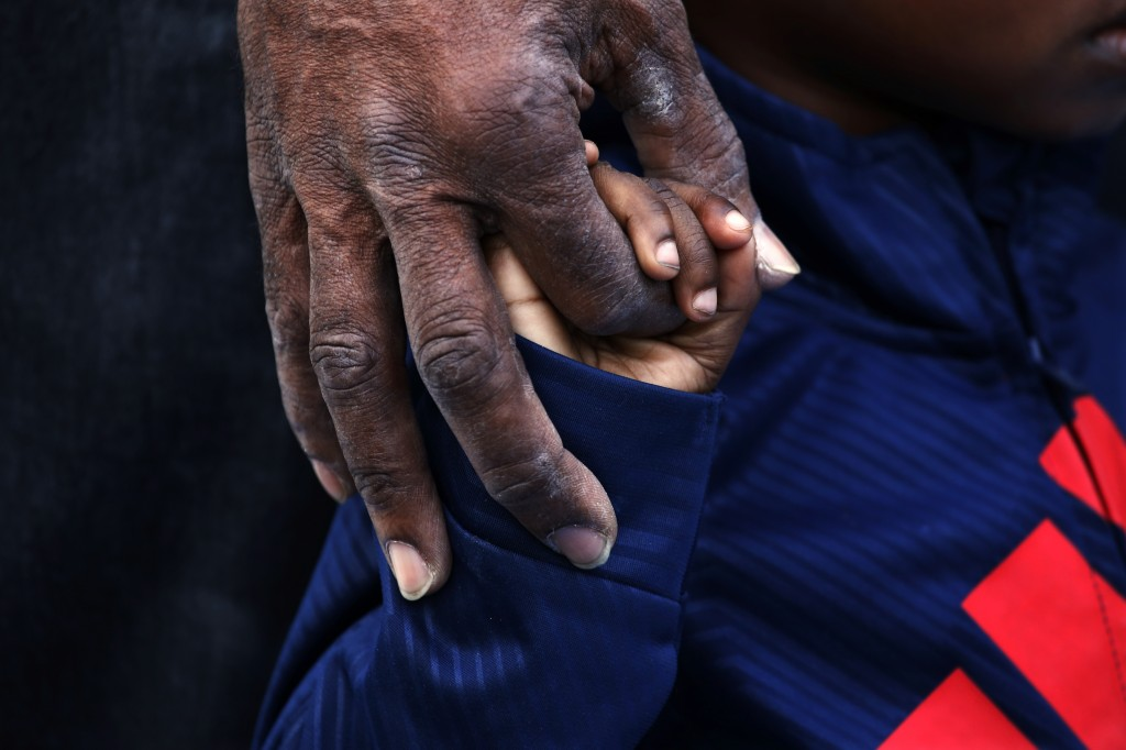 Hasan Smith holds the hands of his grandson, D'Angelo Brown, 2, as they listen to a band at a housewarming party in Smith's back yard in Chicago on Se...