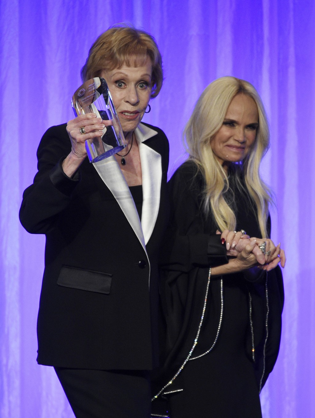 "Honoree Carol Burnett, left, is led offstage by presenter Kristin Chenoweth during ""The Paley Honors: A Special Tribute to Television's Comedy Legends..."