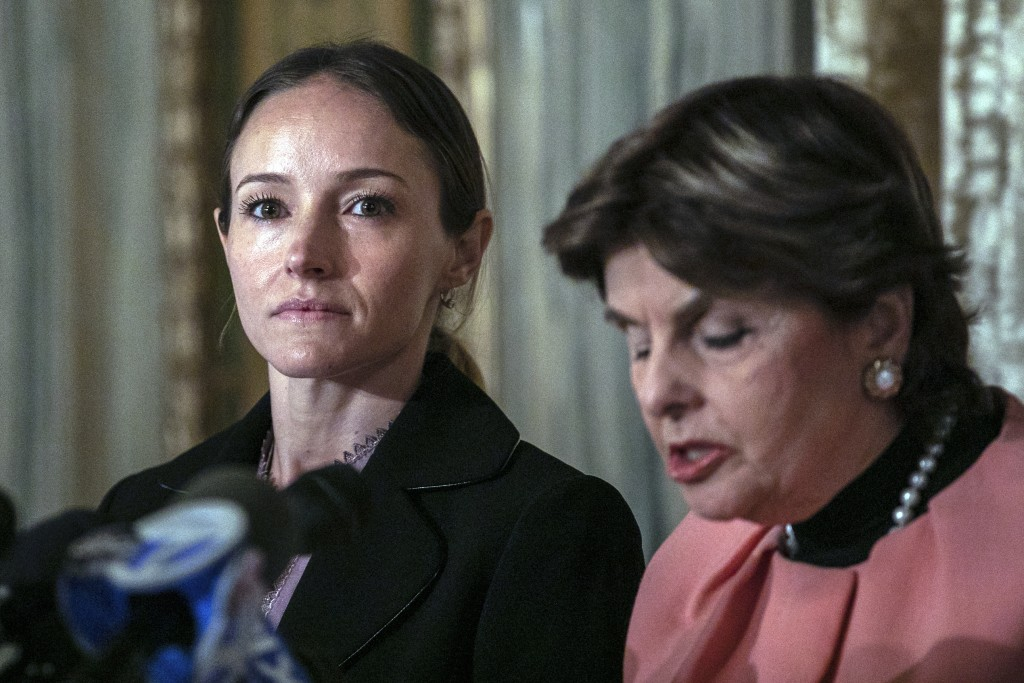 Teala Davies, left, listens to her attorney Gloria Allred, right, speak news conference, Thursday, Nov. 21, 2019, in New York, about the filing of a l...