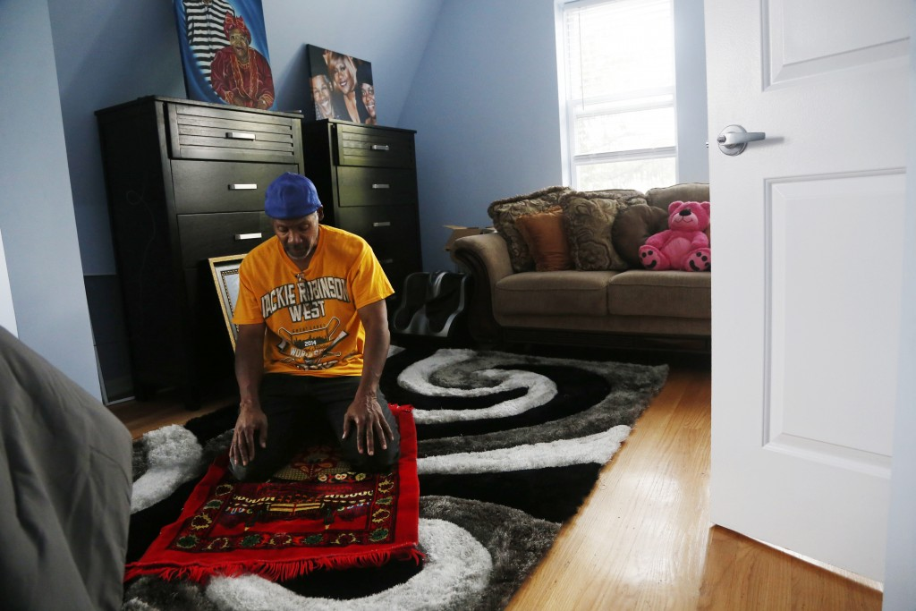 Hasan Smith prays in the bedroom of his new home in Chicago on Sept. 28, 2019. Smith converted to Islam while in prison and serving more than 27 years...