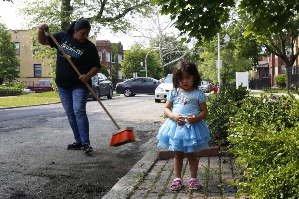 Jessica Garcia, left, sweeps the street in front of her new home as daughter Kayleen Garcia, age 2, stands in the foreground in Chicago on June 1, 201...
