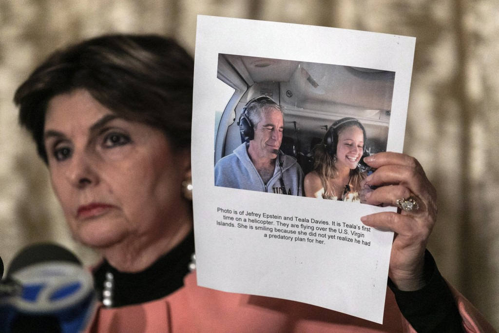 Attorney Gloria Allred, holds a picture of Jeffrey Epstein and her client Teala Davis during a news conference, Thursday, Nov. 21, 2019, in New York, ...