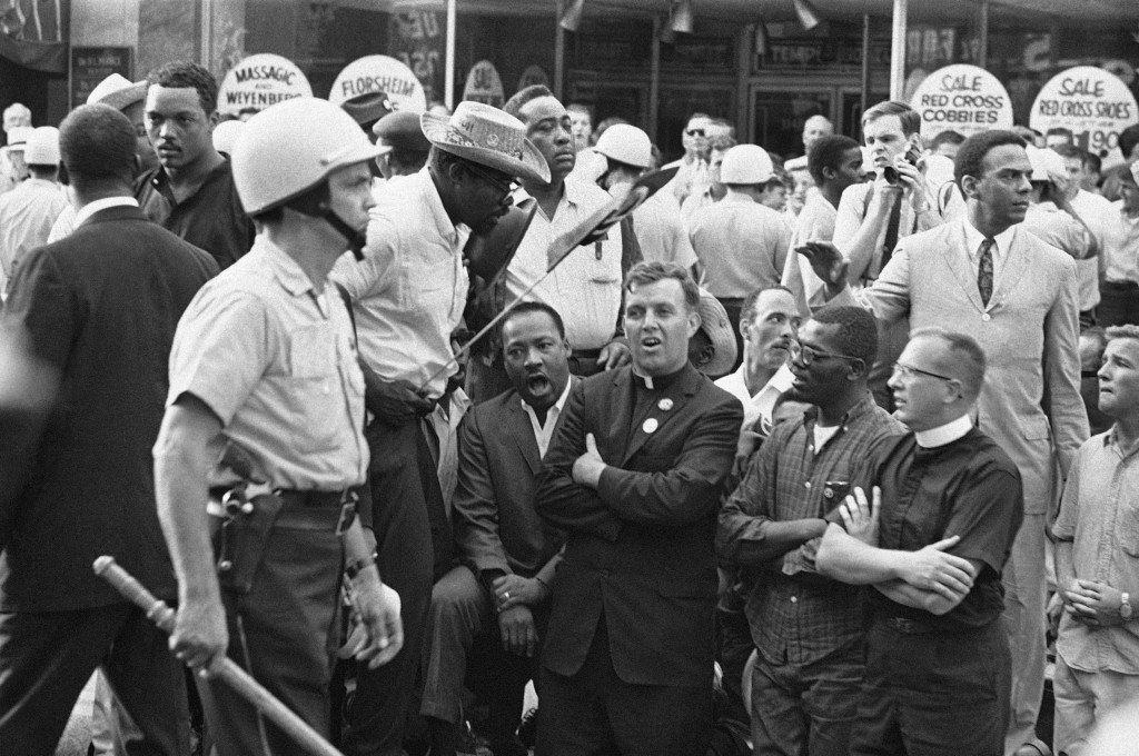 FILE - In this Aug. 6, 1966, file photo, Martin Luther King, Jr., kneeling on left, leads civil rights marchers in singing and praying in front of rea...