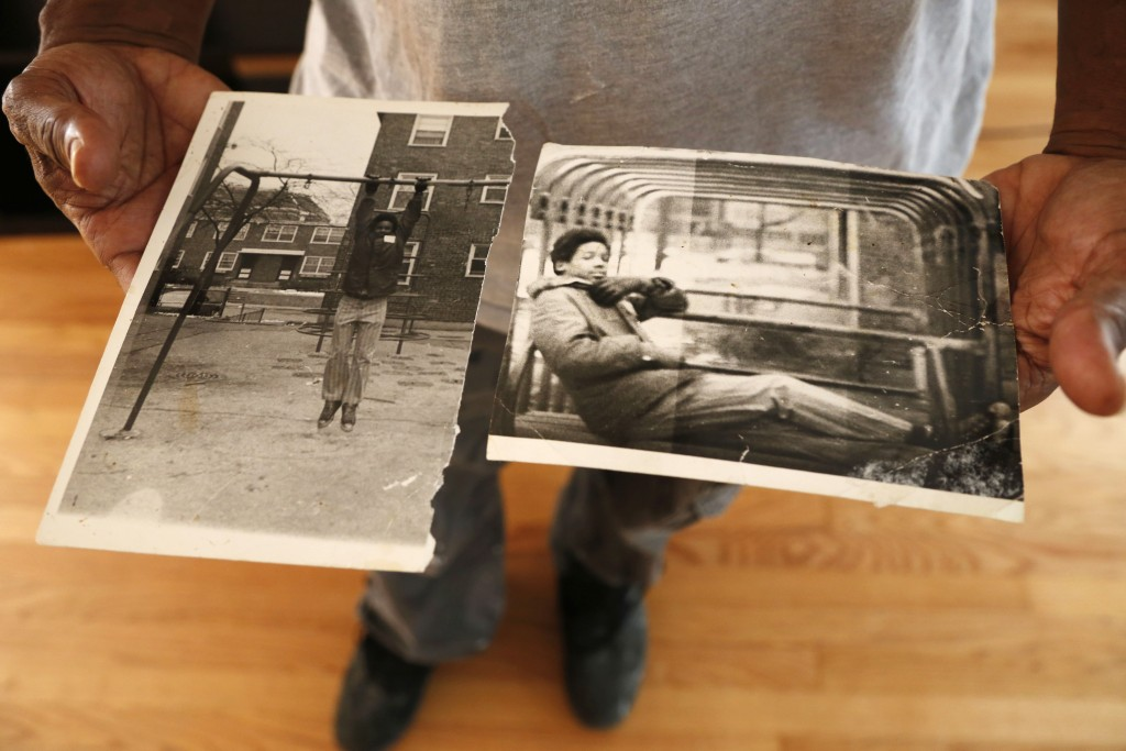 Hasan Smith holds photos on Sept. 11, 2019, that a friend took of him in 1974 for a school project in Chicago. He was 15 and already involved with gan...